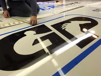 Laying vinyl on a 10'x15′ sign for Gateway Products